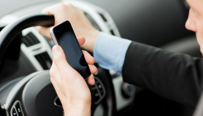 How you communicate matters. Image of driver at wheel while looking at mobile phone.